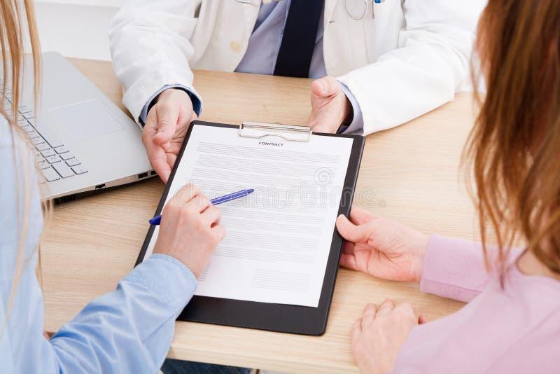 Lekarka z pacjentami w medycznym biuro znaku kontrakt Healthca fotografia stock
