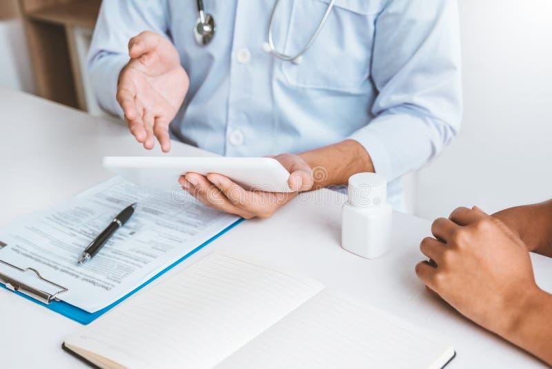 Lekarka z pacjentem przedstawia o traktowanie wytycznach na cyfrowej pastylce przy biurem obraz stock