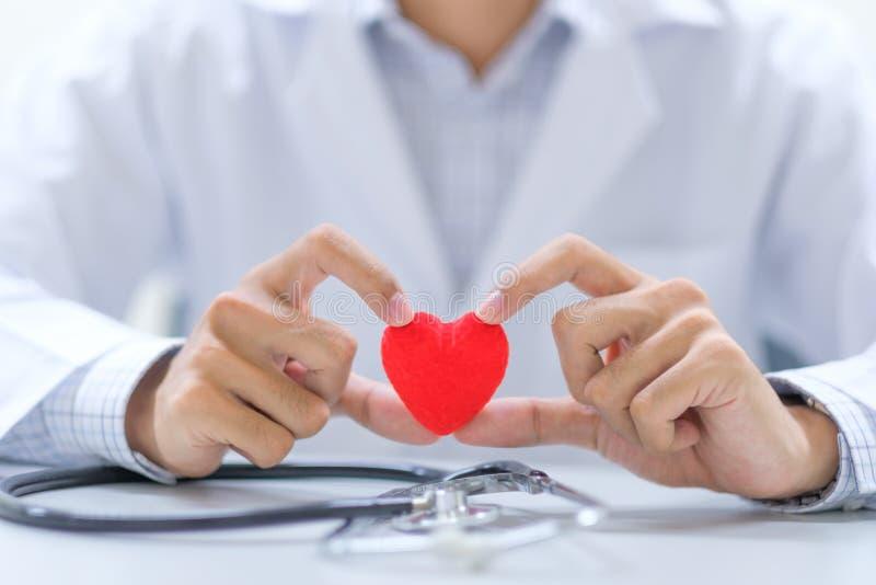 Lekarka z stetoskop ręki mienia czerwonym kierowym kształtem w szpitalu zdjęcie royalty free