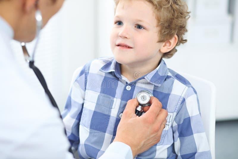 Lekarki i dziecka pacjent Lekarz egzamininuje chłopiec stetoskopem Medycyny i dziecka ` s terapii pojęcie fotografia stock