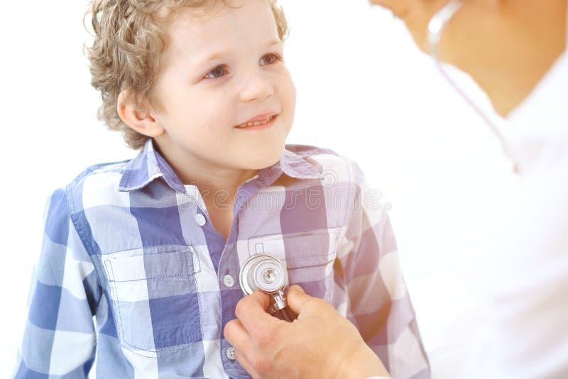 Lekarki i dziecka pacjent Lekarz egzamininuje chłopiec stetoskopem Medycyny i dziecka ` s terapii pojęcie zdjęcie stock