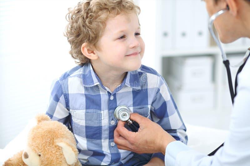 Lekarki i dziecka pacjent Lekarz egzamininuje chłopiec stetoskopem Medycyny i dziecka ` s terapii pojęcie obraz royalty free
