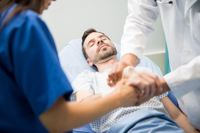 Lekarki pracuje na unconsious pacjencie zdjęcia stock