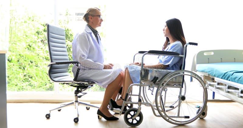 Lekarki są pytać i wyjaśniać o chorobie żeński pacjent na wózku inwalidzkim przy szpitalem obraz royalty free