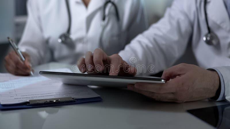 Lekarki siedzi przy stołem, pracujący na pastylki i plombowanie papieru formach, praca zespołowa fotografia stock