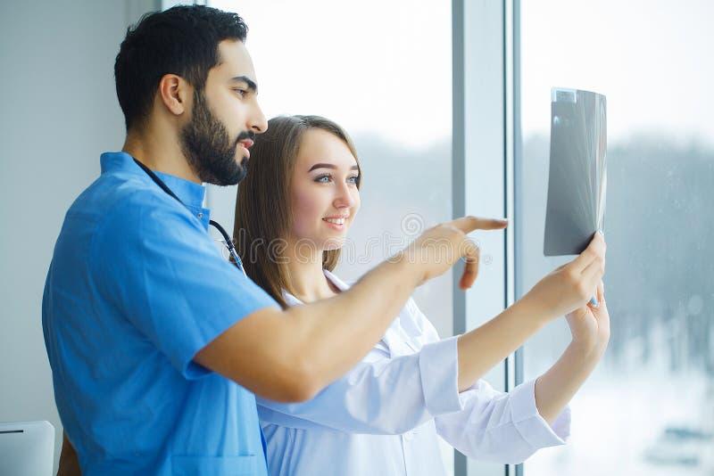 Lekarki zespalają się egzamininujący cierpliwego ` s promieniowanie rentgenowskie zdjęcie stock
