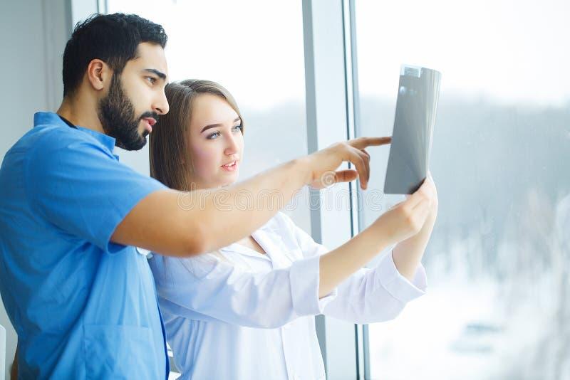 Lekarki zespalają się egzamininujący cierpliwego ` s promieniowanie rentgenowskie fotografia stock