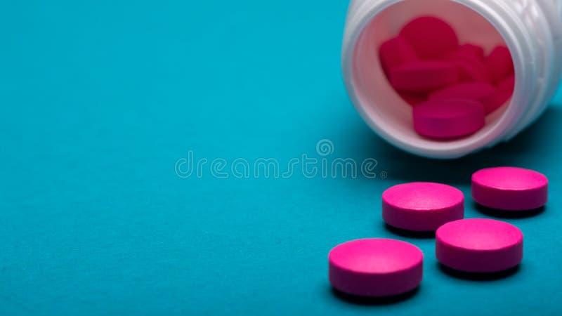 Lekarstwo butelka i jaskrawe różowe pigułki rozlewaliśmy na zmroku - błękit coloured tło Lekarstwa i recepty pigułek zamknięty up zdjęcie royalty free