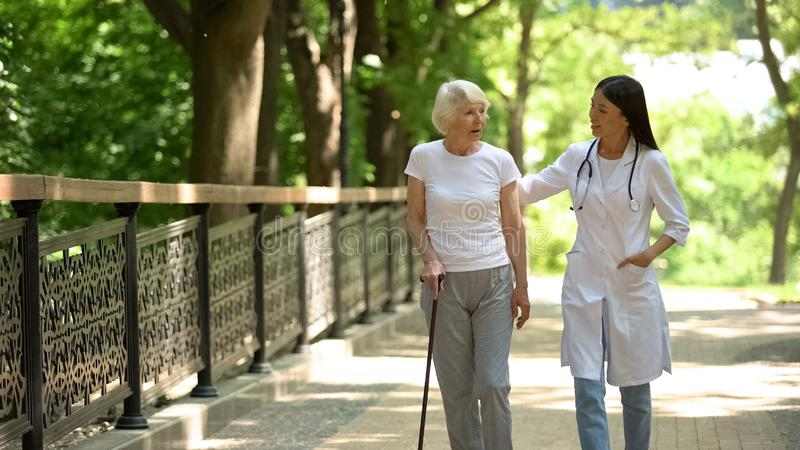 Lekarz chodzący w parku z pacjentką w podeszłym wieku z laską, rehabilitacją zdjęcia stock