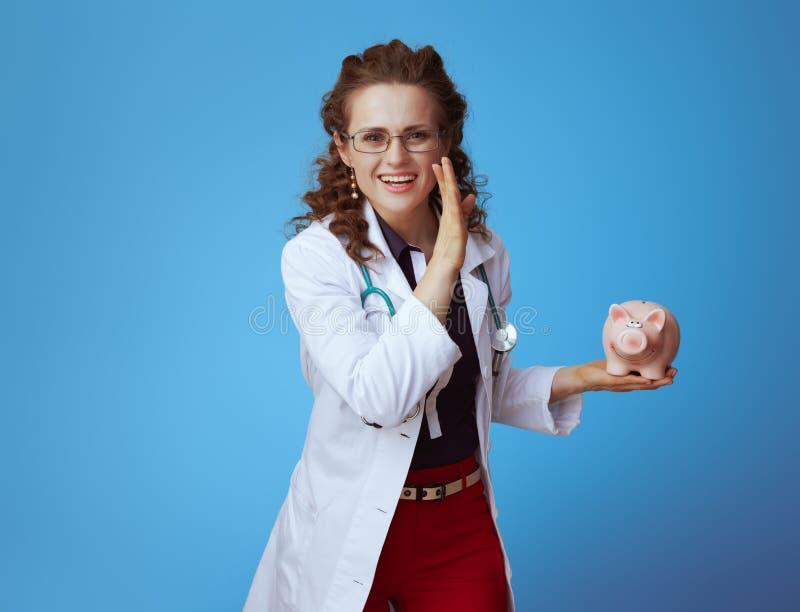 Lekarz medycyny kobieta m?wi podniecaj?c? wiadomo?? z prosi?tko bankiem obraz stock