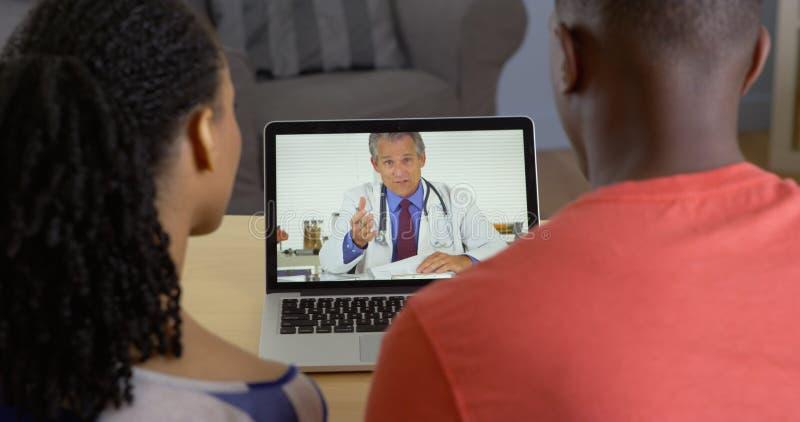 Lekarz opowiada z młodą czarną parą o medycznych zagadnieniach zdjęcie stock