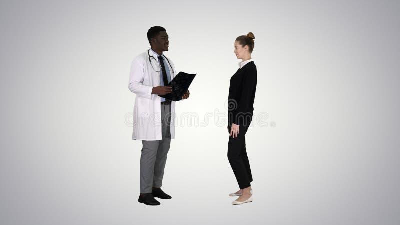 Lekarz pokazuje pacjentowi promieniowanie rentgenowskie wynika cierpliwych liście na gradientowym tle Wtedy fotografia royalty free