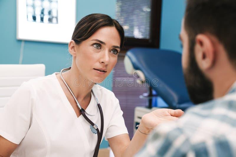 Lekarz rozmawia z pacjentem w szpitalu przy stole. fotografia stock