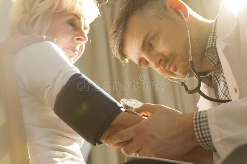 Lekarz sprawdza ciśnienie krwi fotografia royalty free
