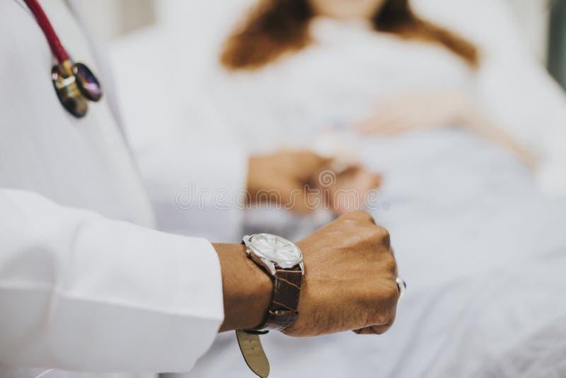 Lekarz sprawdza jej pacjenta puls obrazy royalty free