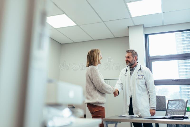 Lekarza chwiania ręki z pacjentem w klinice obrazy stock