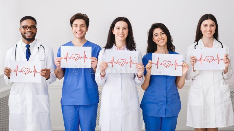 Lekarzi praktykujący Trzyma papiery Z Cadiograms bicie serca zdjęcia royalty free