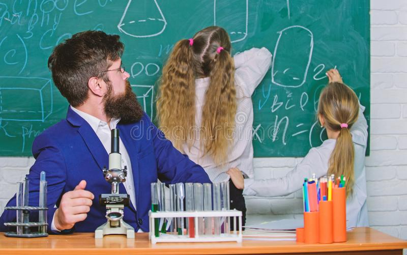 lekcja st??enia obrazu ucznia M?ski nauczyciel daje intymnej lekcji ma?e dzieci Ma?e uczennicy recytuje lekcj? przy chalkboard obrazy stock