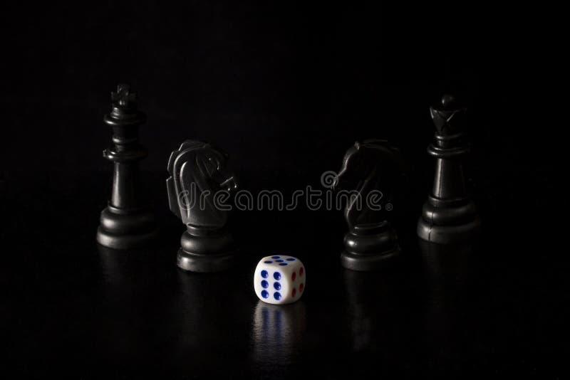 Lekcy kostka do gry i czarni szachowi kawałki na ciemnym tle zdjęcie royalty free