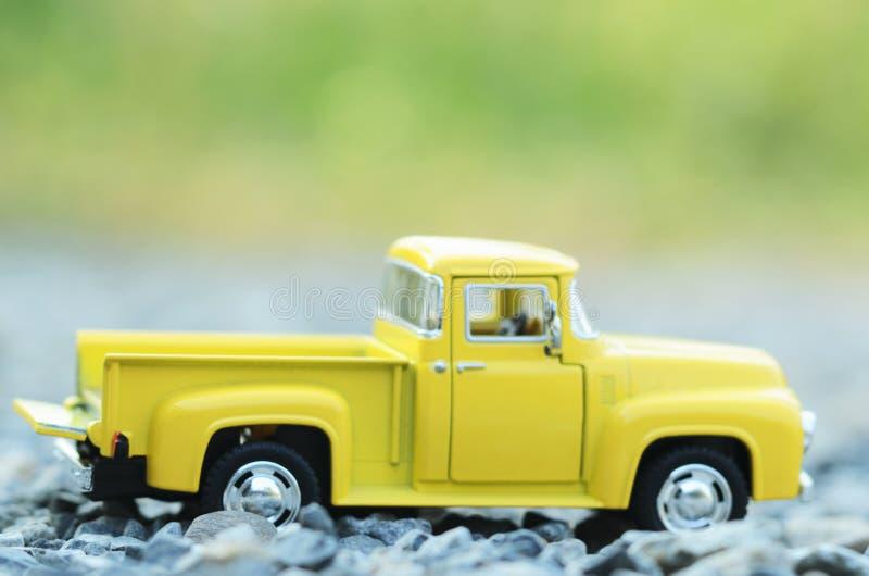 Leker med den gula lastbilen för suddighet ljusa bakgrunder för grön bokeh royaltyfria bilder