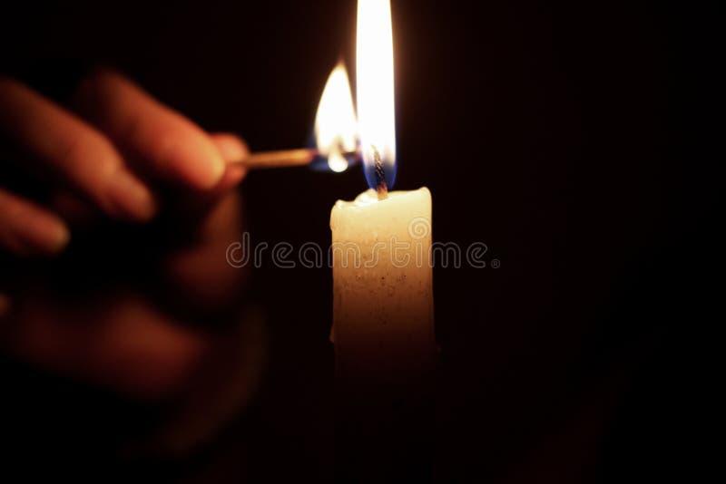 Lekka świeczka w ciemności z dopasowaniem obraz stock