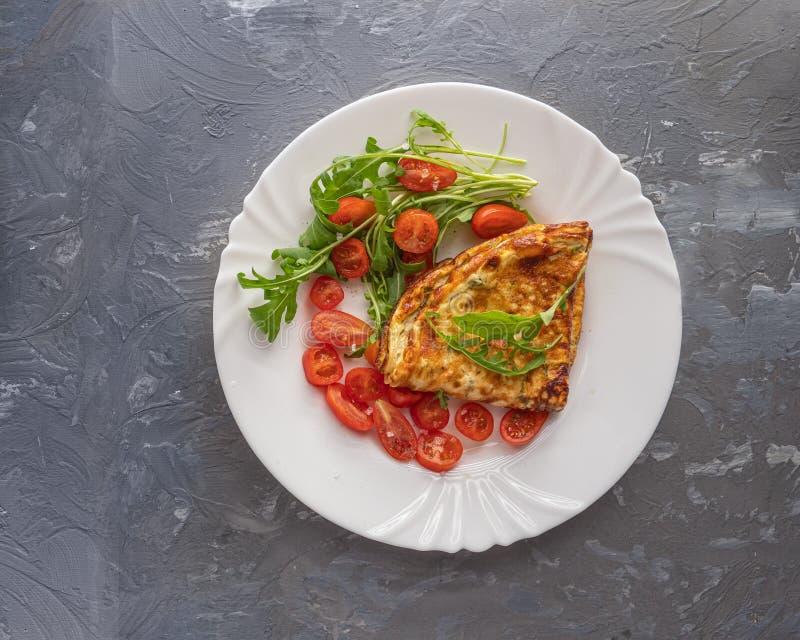 Lekki śniadanie omlet i czereśniowy pomidor na wielkim bielu talerzu na szarym tle, strzał od zamkniętego pasma, odgórny widok Li zdjęcie royalty free