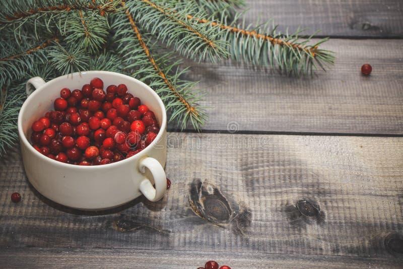 Lekki drewniany stołowy wierzchołek z filiżanką świeże czerwone jagody dekorował z świerkowym sprig zdjęcie royalty free