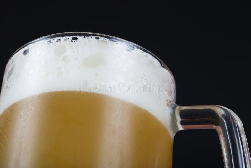 Lekki piwo w kubku na ciemnym tle obraz stock