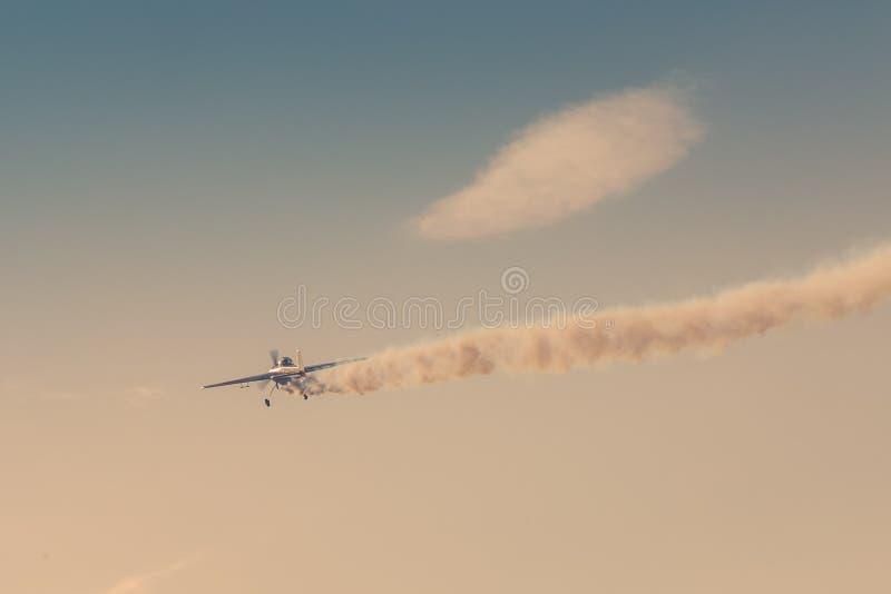 Lekki samolot lata puszek opuszcza za ja ciemnego dym jako ilustracja trzask intymny strumień obraz tonujący zdjęcia stock