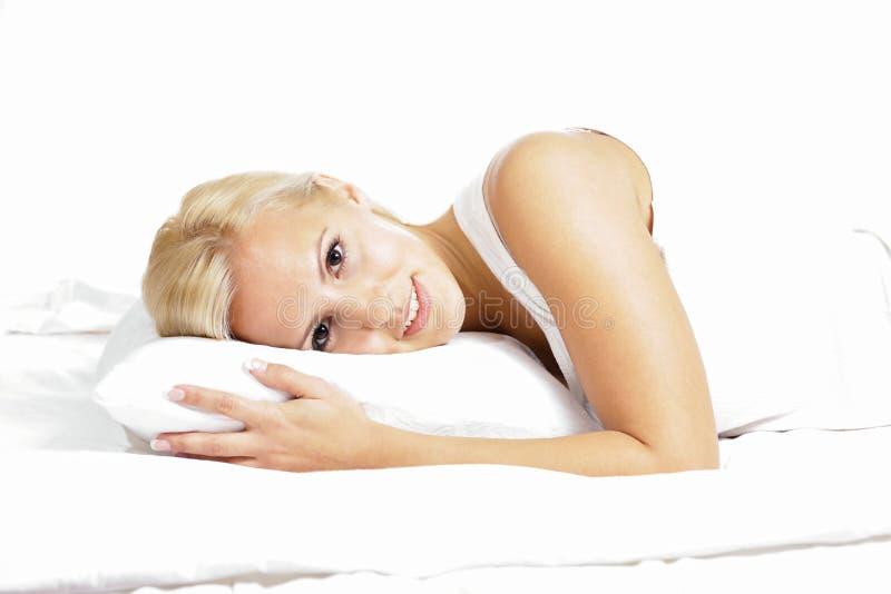 Lekki włosiany kobieta model ono uśmiecha się i kłama na poduszce, fotografia stock