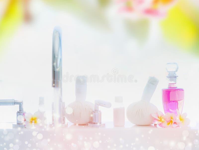 Lekki zdroju lub wellness tło z wanną, ciało opieki produkty, masaż stempluje i frangipani kwitnie zdjęcia stock
