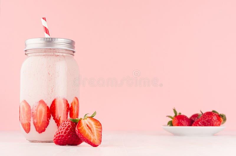 Lekkiego nabiału truskawkowy napój w modnym słoju z dojrzałymi kawałkami jagodowymi na spodeczku, czerwona pasiasta słoma, srebny zdjęcie royalty free