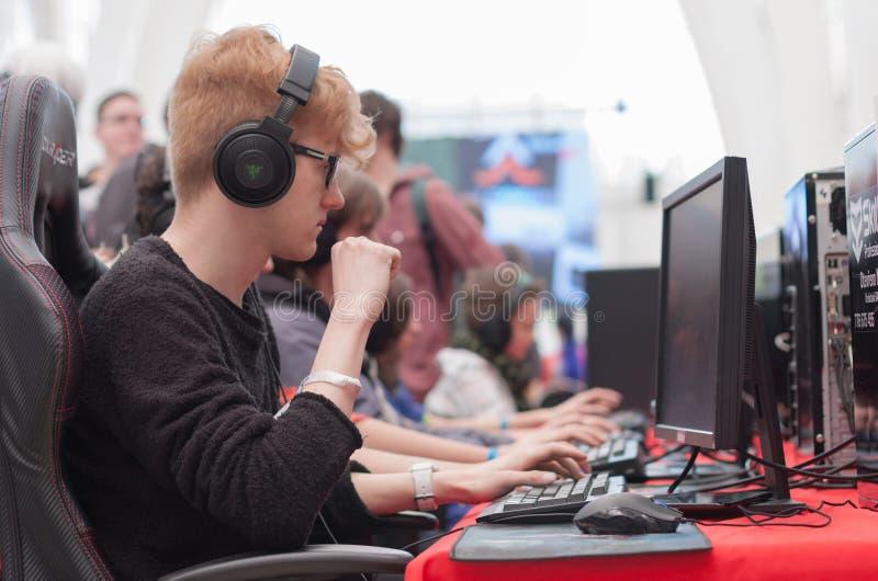 Leklek för ung man på persondatorn på Animefest royaltyfri bild