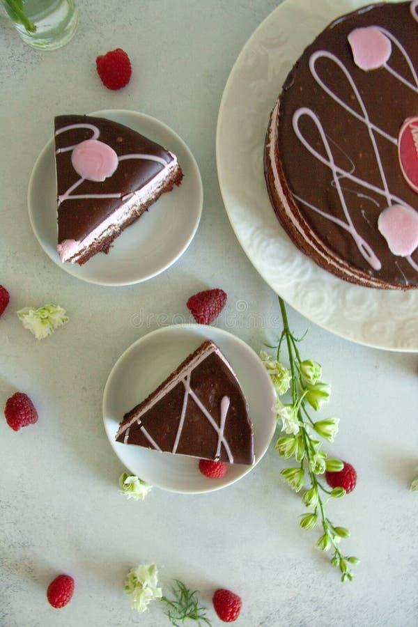 Lekmanna- choklad för lägenhet och hallonstycke av kakan på en vit platta med vita blommor och nya bär royaltyfri fotografi