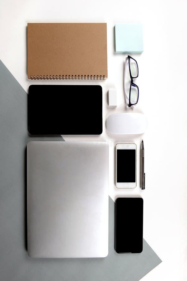 Lekmanna- foto för lägenhet av kontorstabellen med bärbar datordatoren, anteckningsbok, digital minnestavla, mobiltelefon, blyert royaltyfria foton
