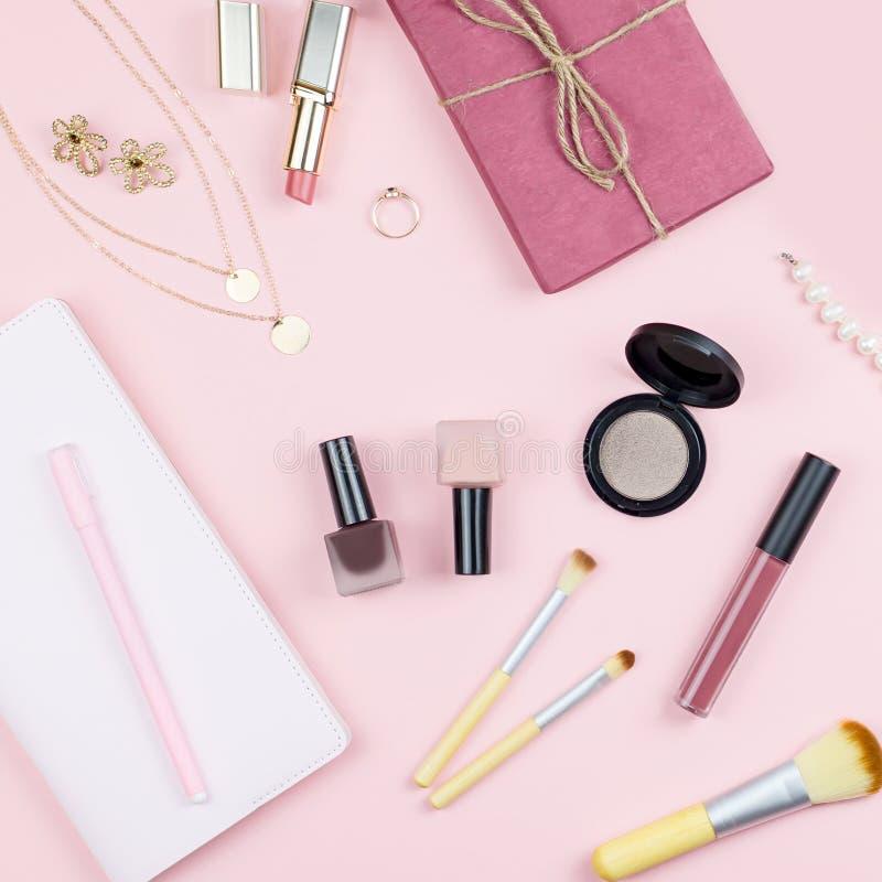 Lekmanna- inrikesdepartementetskrivbord för lägenhet Kvinnlig workspace med anteckningsboken, modetillbehör och sminkprodukter på royaltyfri bild