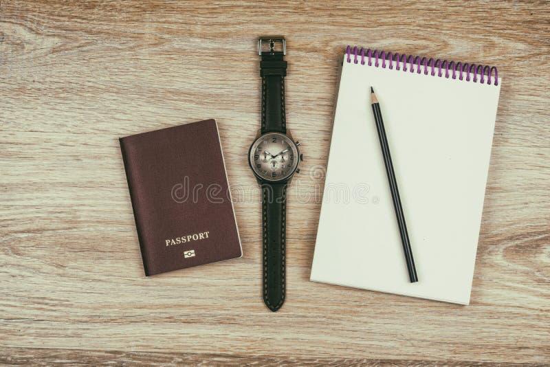 Lekmanna- lägenhet Anteckningsbok med blyertspennor, passet och armbandsuret royaltyfria bilder