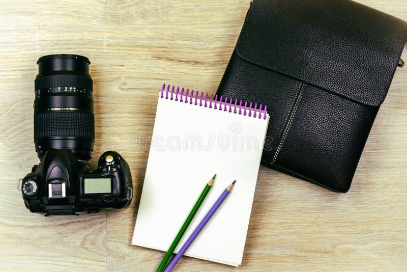 Lekmanna- lägenhet SLR kameran, notepaden, två blyertspennor och en påse för man` s ligger på texturen av trät royaltyfria bilder