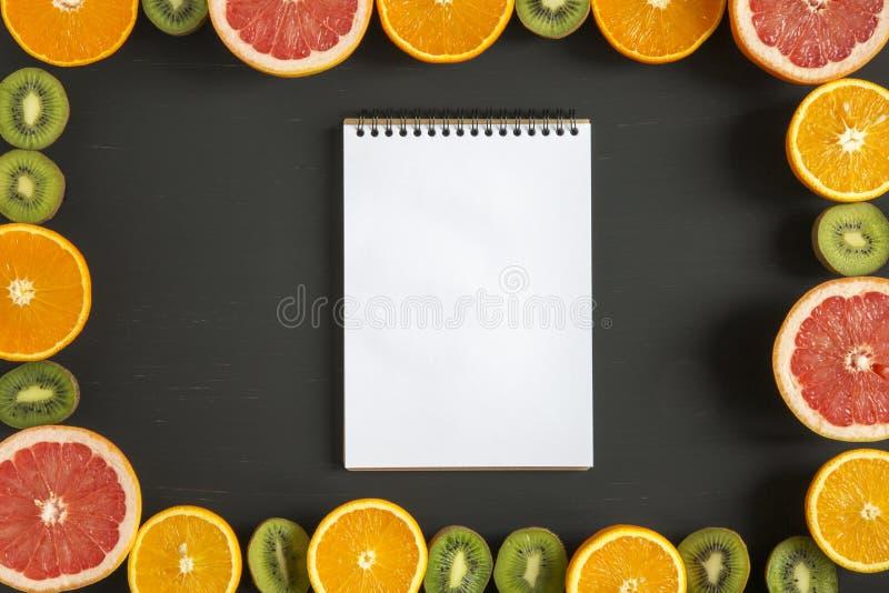 Lekmanna- lägenhet Top beskådar Anteckningsbok med skivade färgrika nya frukter: kiwi, apelsin, grapefrukt och mandarin på svart  royaltyfri fotografi