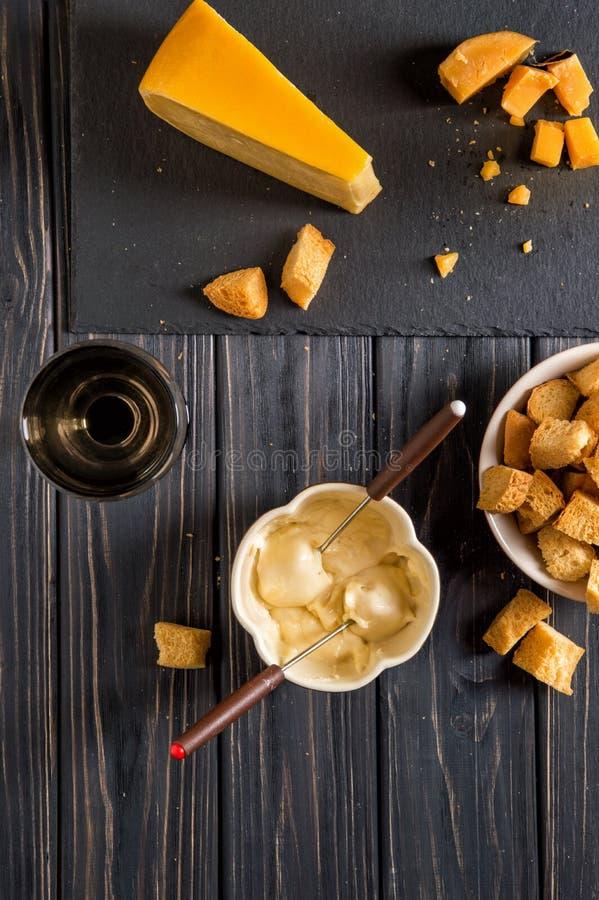 Lekmanna- lägenhet Traditionell fransk ostfondue Krutongen doppade in i den varma ostfondue på enstemmed gaffel fotografering för bildbyråer