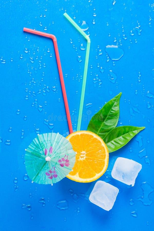 Lekmanna- moget saftigt snitt för lägenhet i halva apelsingräsplansidor som dricker sugrör som smälter paraplyet för iskuber på b fotografering för bildbyråer