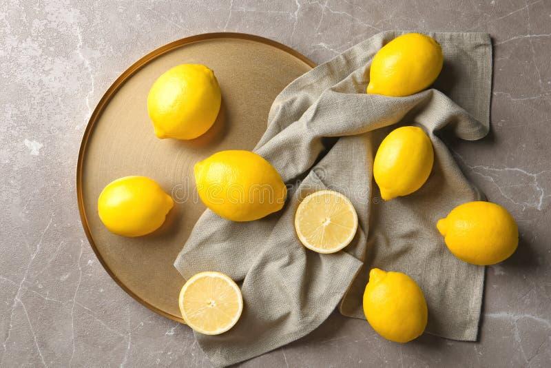 Lekmanna- sammansättning för lägenhet med citroner, tyg och den guld- plattan royaltyfri bild
