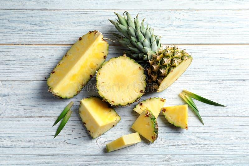 Lekmanna- sammansättning för lägenhet med ny skivad ananasträbakgrund fotografering för bildbyråer