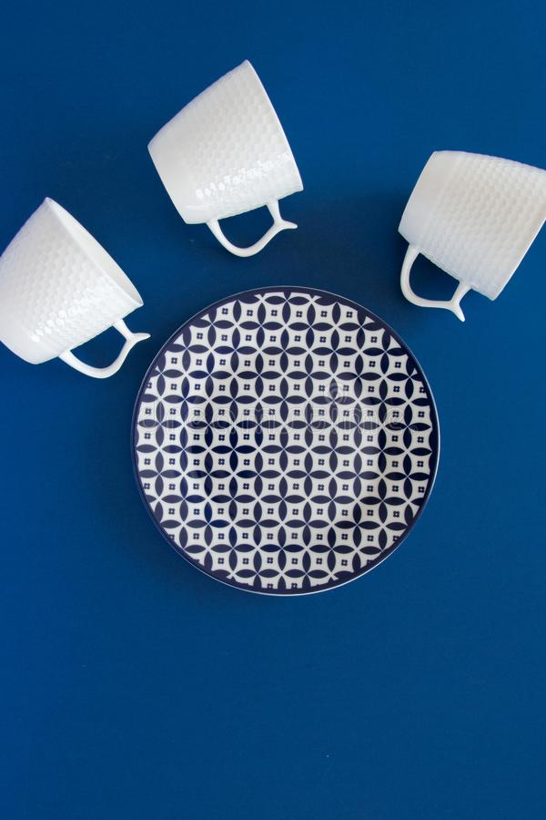 Lekmanna- sikt för över huvudet lägenhet av koppar för ren bordsservisplatta och för vitt kaffe på mörkt - blå bakgrund arkivfoto