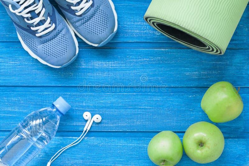 Lekmanna- sportskor för lägenhet, flaska av vatten, mattt och hörlurar på blått arkivfoto