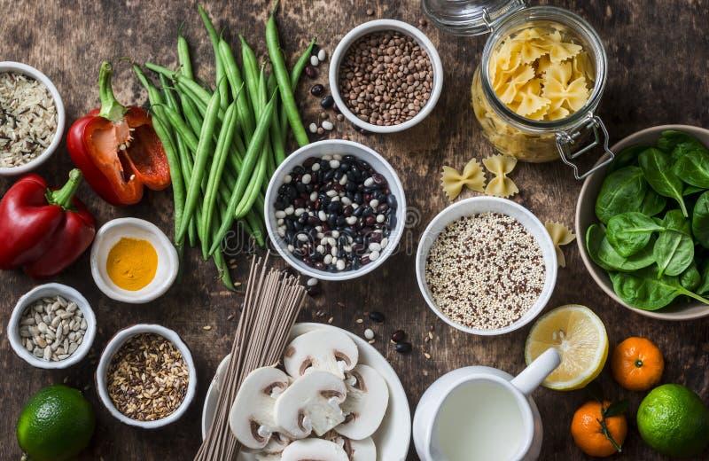 Lekmanna- vegetarisk sund matuppsättning för lägenhet - korn, grönsaker, frukt, pasta, frö på en brun träbakgrund, bästa sikt Sun arkivbild