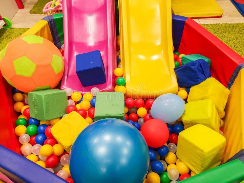 Lekplats barns glidbanor, ett lekomr?de av f?rgrika plast- bollar Gladlynta barns fritid med bollar i lekp?len, nolla royaltyfria foton
