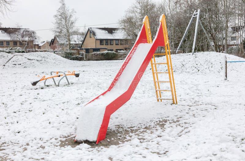 Lekplats i dagiset för barn i vintern - glidbana royaltyfria foton