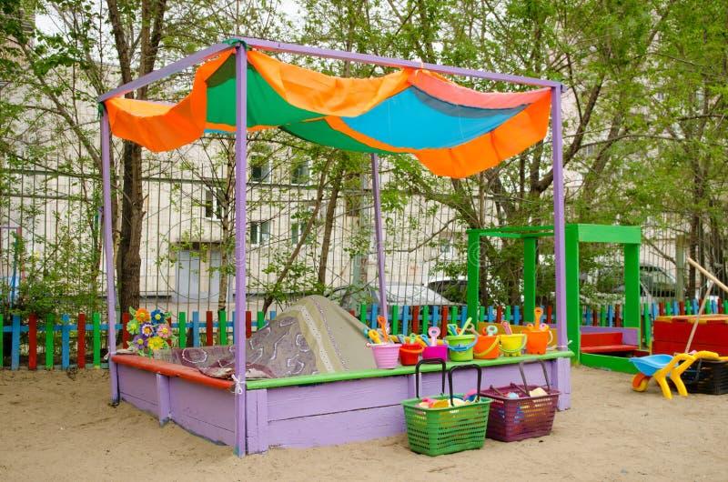 Lekplats med sandlådan med markisen med skyfflar, hinkar för barns lekar arkivbild