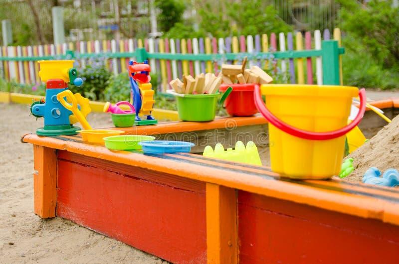 Lekplats med sandlådan med skyfflar, hinkar för barns lekar fotografering för bildbyråer